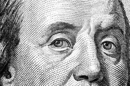 Close up view Portrait of Benjamin Franklin on the one hundred dollar bill. Background of the money. 100 dollar bill with Benjamin Franklin eyes macro shot. Black and white