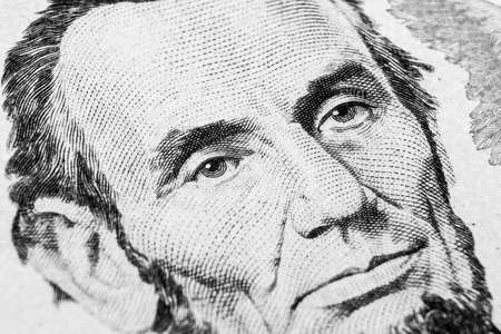 Close up view Portrait of Abraham Lincoln on the one five dollar bill. Background of the money. 5 dollar bill with Abraham Lincoln eyes macro shot. Money background. Face portrait. Black and white Фото со стока