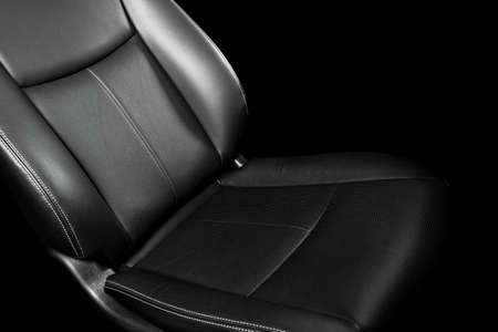 Black leather interior of the luxury modern car. Perforated Leather comfortable seats with yellow stitching isolated on black background. Modern car interior details. Car detailing. Car inside