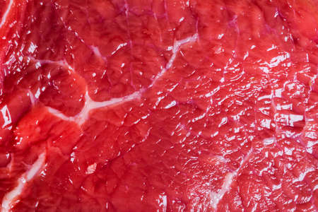 Beef raw red meat closeup texture background. Fresh beef piece in closeup. Marbled meat texture. Raw fillet of beef steak.