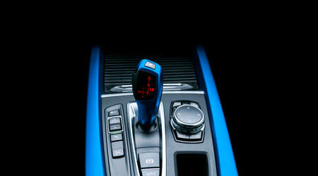 Blue Automatic gear stick of a modern car. Modern car interior details. Close up view. Car detailing. Automatic transmission lever shift isolated on black background. Black leather interior with stitching.