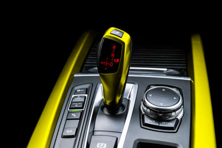 Yellow Automatic gear stick of a modern car. Modern car interior details. Close up view. Car detailing. Automatic transmission lever shift isolated on black background. Black leather interior with stitching.