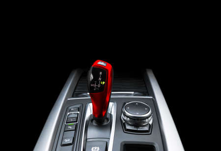 Red Automatic gear stick of a modern car. Modern car interior details. Close up view. Car detailing. Automatic transmission lever shift isolated on black background. Black leather interior with stitching.