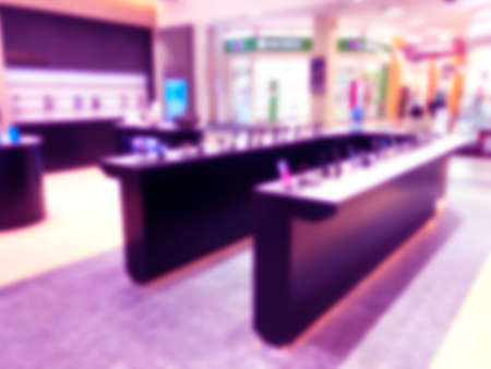 Abstract blur background with mobile store boutique in shopping mall. Eletronic department store interior with bokeh light blurred background. Defocused blur background.  Blurry interior view retail shop