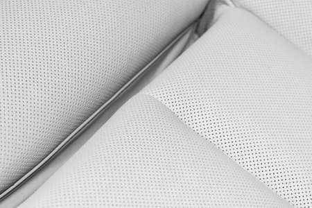 White leather interior of the luxury modern car. Perforated white leather comfortable seats with stitching. Modern car interior details. Car detailing. Car inside