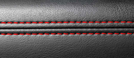 Modern sport car black leather interior. Part of leather car seat details with red stitching. Car detailing.