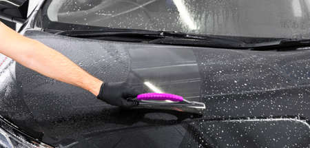 A man cleaning car with plastic sponge. Car detailing or valeting concept. Selective focus. Car detailing. Cleaning with sponge and cloth. Worker cleaning. Car wash concept solution to clean