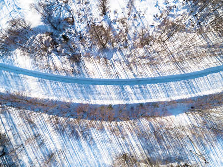Aerial view of a winter road in the forest. Winter landscape countryside. Aerial photography of snowy forest with road. Captured from above with a drone. Aerial photo. Winter snow texture. Standard-Bild