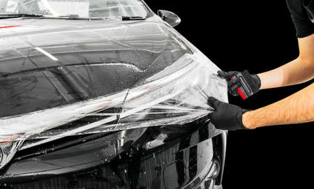 Car wrapping specialist putting vinyl foil or film on car. Protective film on the car. Applying a protective film to the car with tools. Car detailing. Transparent film. Car paint protection. isolated