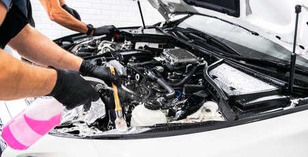 Un hombre limpiando el motor del coche con champú y cepillo. Detalle de coche o concepto de valet. Enfoque selectivo. Detallando el coche. Limpieza con esponja. Trabajador de limpieza. Solución de concepto de lavado de coches para limpiar
