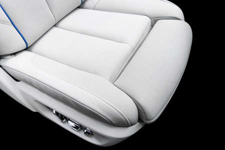 White leather interior of the luxury modern car. Perforated white leather comfortable seats with stitching isolated on black background. Modern car interior details. Car detailing. Car inside