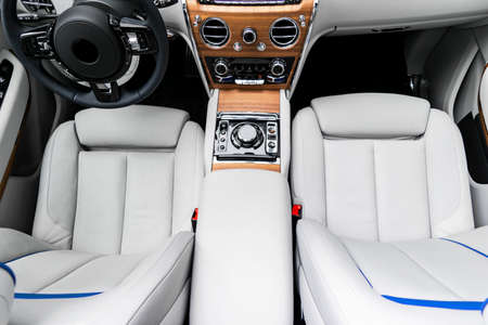 Modern luxury car white leather interior with natural wood panel. Part of leather car seat details with stitching. Interior of prestige modern car. White perforated leather. Car detailing. Car inside