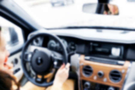 Blurred image of car interior with woman driving. Dashboard. Blur, defocused transportation background. Driving inside car. Bokeh light background 版權商用圖片