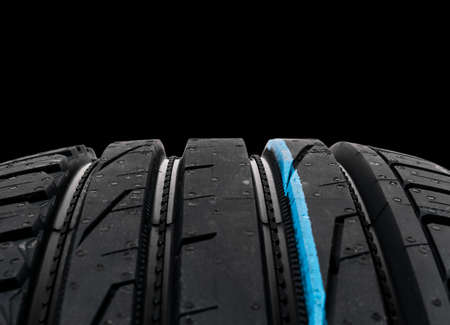 Studio shot of a set of summer car tires on black background. Tire stack background. Selective focus. Car tyre protector close up. Black rubber tire. Brand new car tires. Close up black tyre profile. Car tires in a row