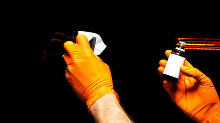 Autopolierwachsarbeiterhände, die Auto polieren. Polier- und Polierfahrzeug mit Keramik. Professionelle Autopflege. Mann hält einen Polierer in der Hand und poliert das Auto mit Nanokeramik. Werkzeuge zum Polieren Standard-Bild