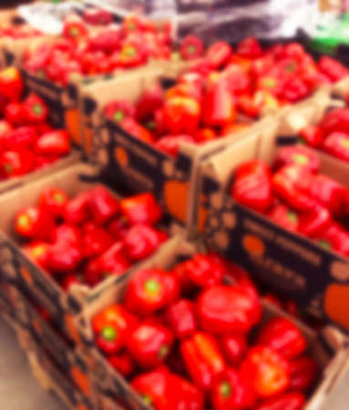 Blurred bacground with Fresh pods of red peppers i supermarket store. Close up. Blur bokeh lights. Abstract blurred supermarket store. Interior shopping mall defocused background