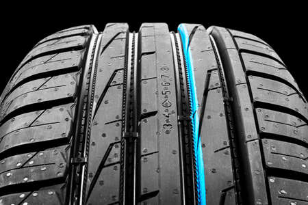 Studio shot of a set of summer car tires on black background. Tire stack background. Car tyre protector close up. Black rubber tire. Brand new car tires. Close up black tyre profile. Car tires in a row