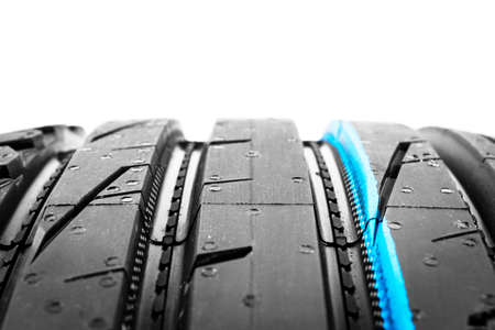 Studio shot of a set of summer car tire on black background. Tire stack background. Car tyre protector close up. Black rubber tire. Brand new car tires. Close up black tyre profile. Car tires in a row