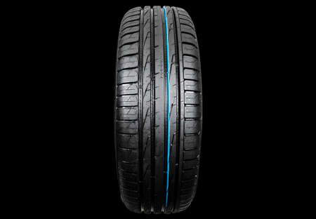 Studio shot of a set of summer car tire isolated on black background. Tire stack. Car tyre protector close up. Black rubber tire. Brand new car tires. Close up black tyre profile. Car tires in a row