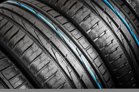 Prise de vue en studio d'un ensemble de pneus de voiture d'été sur fond noir. Fond de pile de pneus. Protecteur de pneu de voiture se bouchent. Pneu en caoutchouc noir. Pneus de voiture neufs. Gros plan du profil de pneu noir. Pneus de voiture d'affilée