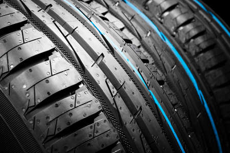 Car tire. Tire stack. Car tyre protector close up. Black rubber tire. Brand new car tires. Close up black tyre profile. Car tires in a row Reklamní fotografie