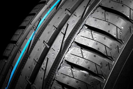 Car tire isolated on black background. Tire stack. Car tyre protector close up. Black rubber tire. Brand new car tires. Close up black tyre profile. Reklamní fotografie