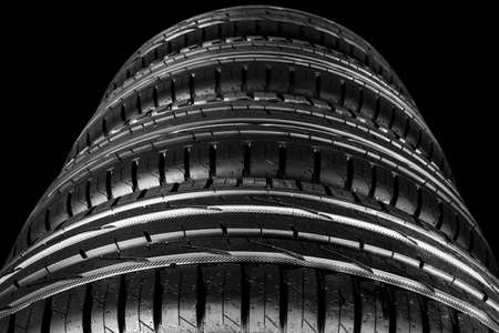 Car tire isolated on black background. Tire stack. Car tyre protector close up. Black rubber tire. Brand new car tires. Close up black tyre profile. Car tires in a row Reklamní fotografie