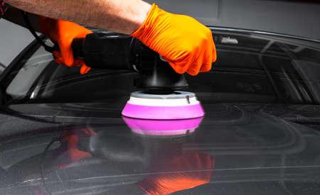 Autopolierwachsarbeiterhände, die vor dem Polieren Schutzband auftragen. Auto polieren und polieren. Professionelle Autopflege. Mann hält einen Polierer in der Hand und poliert das Auto. Werkzeuge zum Polieren Standard-Bild