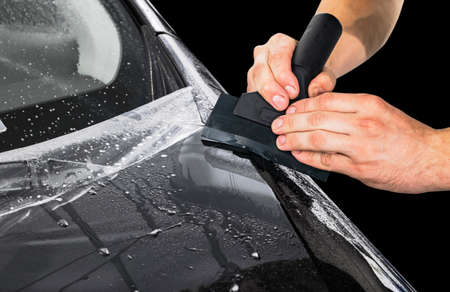 Car wrapping specialist putting vinyl foil or film on car. Protective film on the car. Applying a protective film to the car with tools for work. Car detailing. Transparent film. Car paint protection.