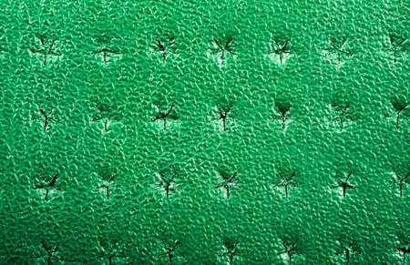 Green perforated leather texture background. Leather close up. Macro shot of shiny leather texture.