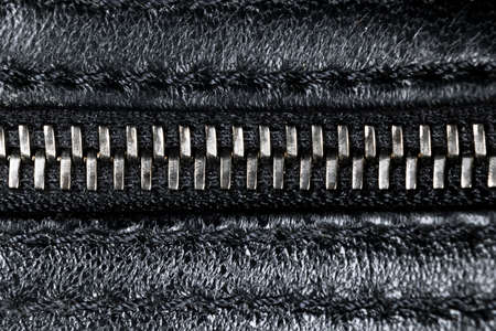 Macro shot of zipper on black leather texture background with stitching. Horizontal background from a close-up of black leather material