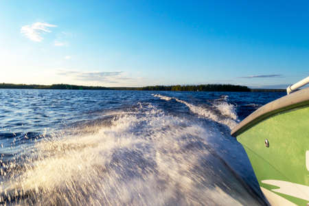 Speeding fishing motor boat with drops of water. Blue ocean sea water wave reflections with fast fishing yacht. Motor boat in the blue ocean. Ocean yacht. Sunset at the sailboat deck 写真素材 - 124865737