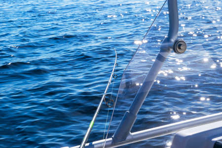Fishing rod in a saltwater private motor boat during fishery day in blue ocean. Successful fishing concept.