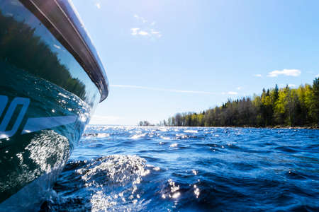 Side view Speeding fishing motor boat with drops of water. Blue ocean sea water wave reflections with fast fishing yacht. Motor boat in the blue ocean. Ocean yacht. Sunset at the sailboat deck 写真素材