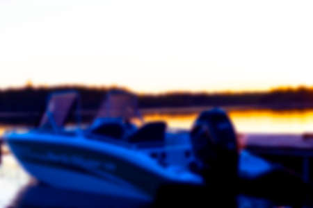 Abstract blurred background with fishing boat parking on the wooden pier. Sunset fishing boat blur background. Abstract blur background with bokeh light