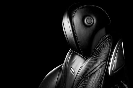 Black leather interior of the luxury modern car. Perforated leather comfortable seats with stitching isolated on black background. Modern car interior details. Car detailing. Black and white 写真素材