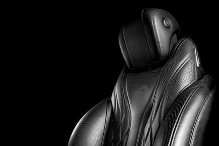 Black leather interior of the luxury modern car. Perforated leather comfortable seats with stitching isolated on black background. Modern car interior details. Car detailing. Black and white 版權商用圖片