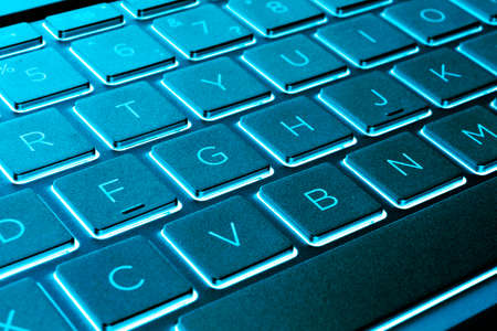 Primer plano de un teclado de computadora portátil plateado moderno. Teclado de computadora portátil. Detalle del nuevo y ergonómico teclado de la computadora. Tonos azules