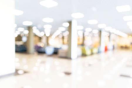 Bokeh sfocato sfocato sullo sfondo della sala espositiva o del corridoio del centro congressi. Architettura interna bianca moderna di fiera commerciale. Sfocatura astratta sfondo moderno ufficio affari