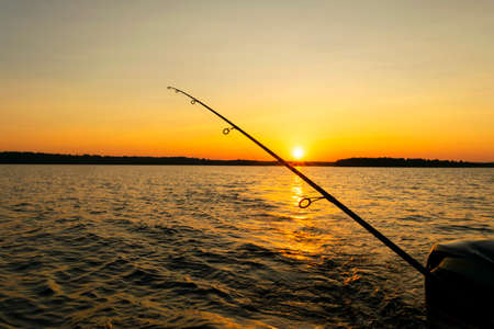 Fishing rod silhouette during sunset. Fishing pole against ocean at sunset. Fishing rod in a saltwater boat during fishery day in the ocean.