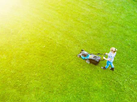 Beautiful girl cuts the lawn. Mowing lawns. Aerial view beautiful woman lawn mower on green grass. Mower grass equipment. Mowing gardener care work tool. Close up view. Aerial lawn mowing Stockfoto
