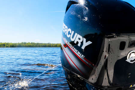 Helsinki, Finland, May 20, 2019: Modern new fishing sport boat with a brand new Mercury FourStroke outboard engine on the lake.