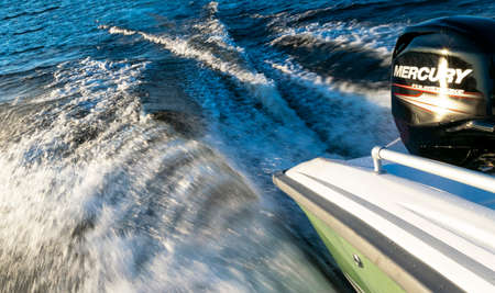 Helsinki, Finland, May 20, 2019: Modern new fishing sport boat with a brand new Mercury FourStroke outboard engine speeding on the lake.