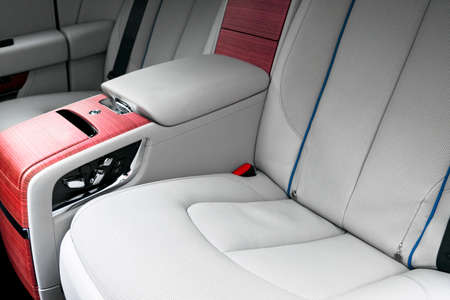 Back passenger seats in modern luxury car. Frontal view. White perforated leather with stitching. Car detailing. Leather comfortable white seats. Car interior details. Car inside