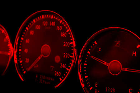 Immagine ravvicinata del tachimetro rosso in un'auto. Cruscotto dell'auto. Dettagli cruscotto con spie di indicazione. Cruscotto auto. Cruscotto con tachimetro, contagiri, contachilometri. Dettagli auto. Archivio Fotografico