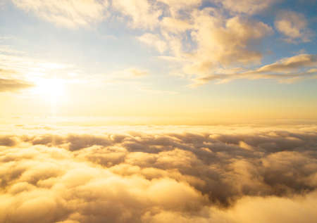Aerial view White clouds in blue sky. Top view. View from drone. Aerial bird's eye view. Aerial top view cloudscape. Texture of clouds. View from above. Sunrise or sunset over clouds 写真素材