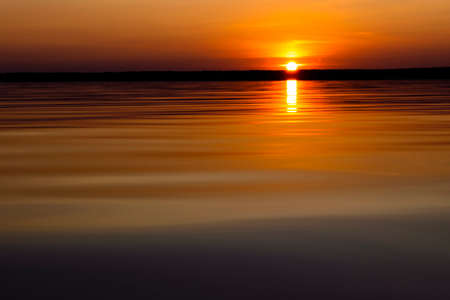 Water surface. View of a Sunset sky background. Dramatic gold sunset sky with evening sky clouds over the sea. View of a Crystal clear sea water texture. Landscape. Small waves. Water reflection Stock fotó
