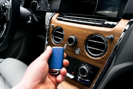 Mans hand holding a wireless ignition car key in white leather interior. Modern Car interior details. Car detailing. Car inside. Car detailing Banco de Imagens