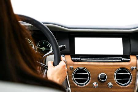 Mani della donna che tengono il volante dell'automobile di un'auto moderna. Mani sul volante di un'auto alla guida. Ragazza alla guida di un'auto all'interno della cabina. Monitorare in auto con schermo vuoto isolato. Display dell'auto con schermo vuoto Archivio Fotografico
