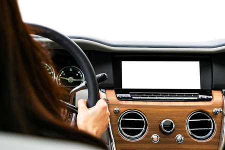 Woman hands holding car steering wheel of a modern car. Hands on steering wheel of a car driving. Girl driving a car inside cabin. Monitor in car with isolated blank screen. Car display with blank screen Banco de Imagens